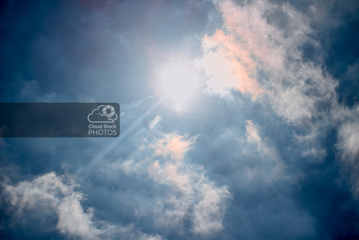 An amazing clouds photo with a mysterious dark blue sky, the sun shining brightly, and crepuscular rays. The sun's glow also highlights clouds in front in white, gray and copper colors, and creates a 3D appearance.