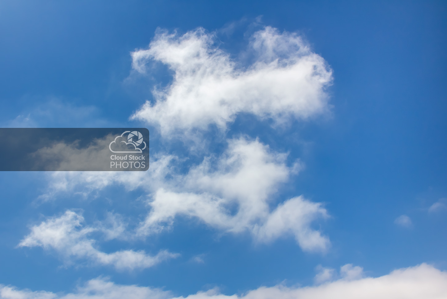Stock photo of white altocumulus clouds in the summer, with a large area of blue sky around the edges that has a cheerful feeling.