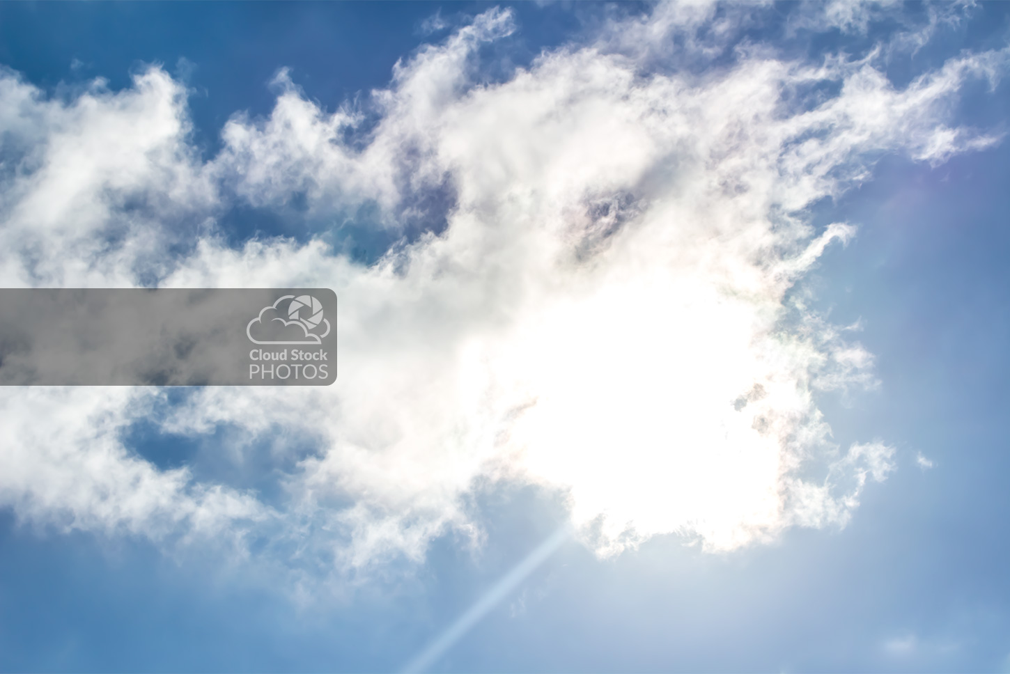 Stock image of beautiful clouds with the sun shining brightly, and subtle shades of yellow, green, orange and purple around the cloud's edges.