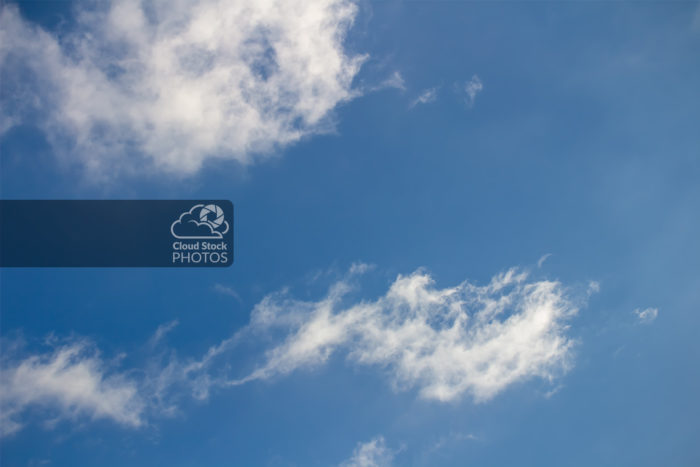 Stock photo of white altocumulus clouds along the top left and bottom of the image, with a large area of blue sky on the top right.
