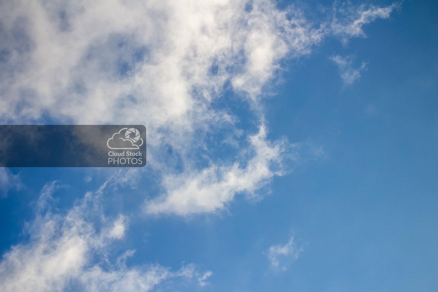 A stock photo of large thin clouds in white and gray along the top and left sides, with a big area of blue sky on the right.
