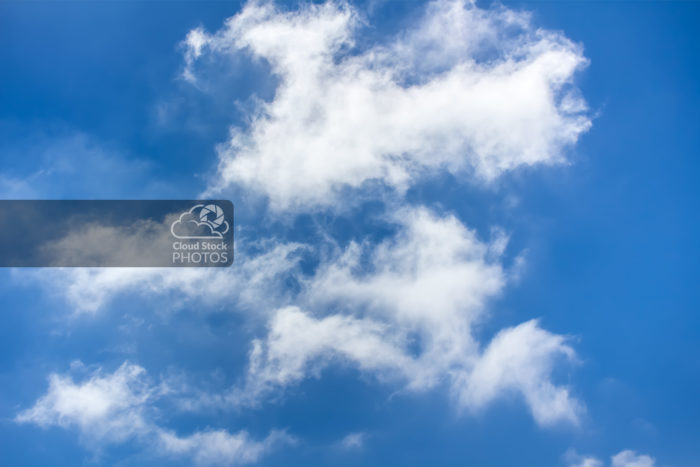 Stock Photo of large billowy clouds, with a vibrant blue sky in the background. A great image to convey joy, fun, adventure and spending time outdoors.