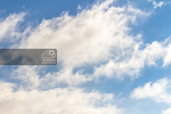 A stock photo of large clouds in various shades of gray and white across the middle and bottom. Wispy ends to the clouds are angled towards the top right of the photo and give the feeling of movement.