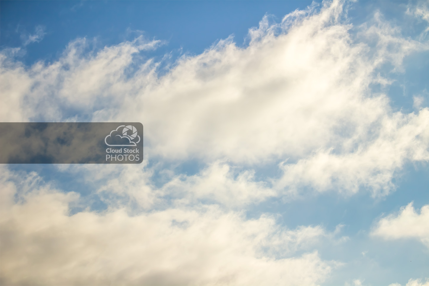 A stock image of large light gray clouds with a slight yellow hue and a pale blue sky background.