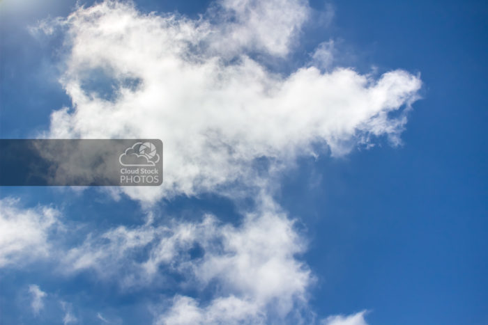 Stock Photo of puffy altocumulus summer clouds with an emerald hue on the left, a deep blue sky in the background on all sides, and the sun's glow in the top-left corner.