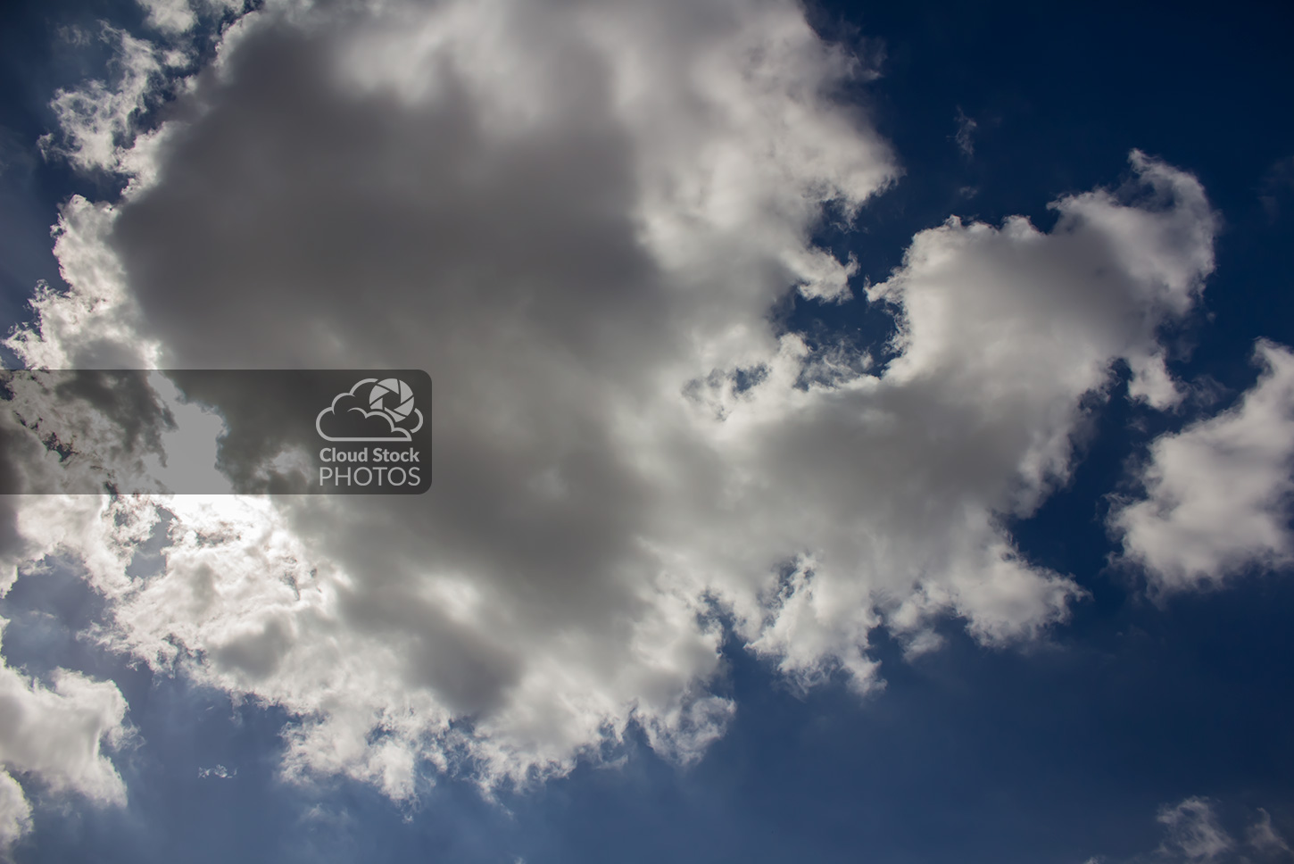 Stock photo of huge cumulus storm clouds. The sun's glow shines brightly through the left side and creates a dramatic glow that beautifully contrasts the thick, dark gray clouds. A somber blue sky in the background along with the dark clouds helps convey a powerful and eerie feeling.