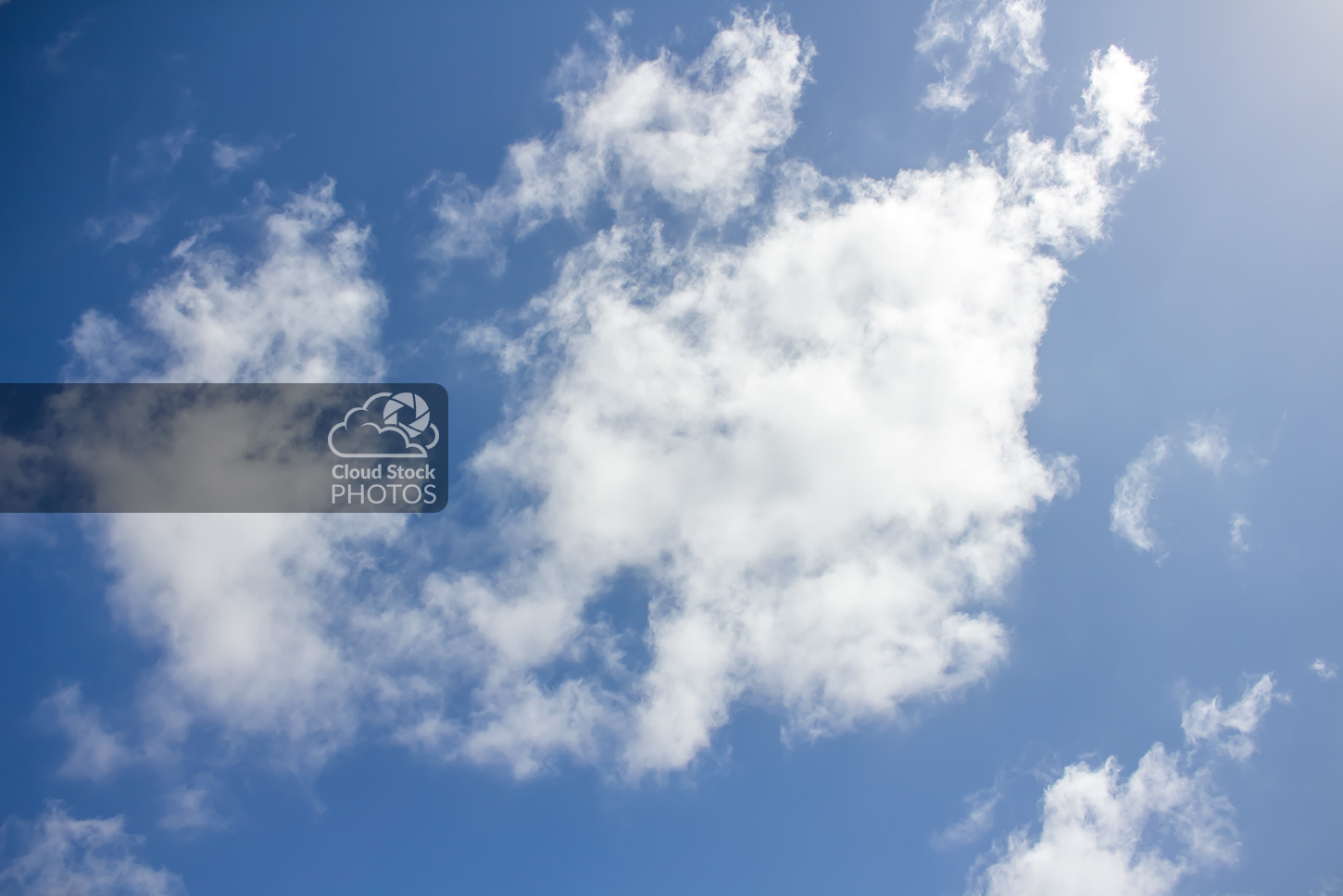 Stock photo of two large altocumulus clouds during the summer. The sun's indirect glow illuminates the image from the top-right side of the image towards the center. And a vivid blue sky is visible on the left.