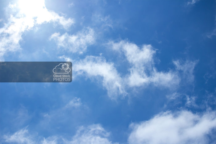 Stock photo of altocumulus clouds in the summer that appear in a diagonal pattern from the top left to bottom right. The sun is shining brightly through the puffy clouds in the top-left corner, with a pleasing blue sky in the background.