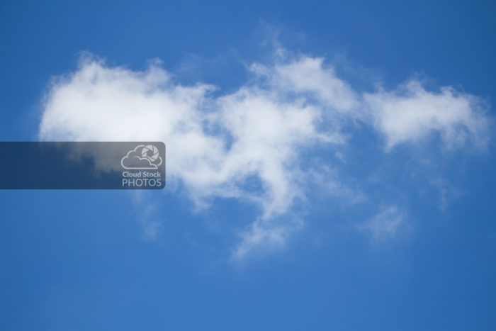 Cloud stock photo of a fluffy altocumulus cloud in the upper-left third of the image, with smaller wispy clouds across the middle and right side, with a relaxing blue summer sky in the background.