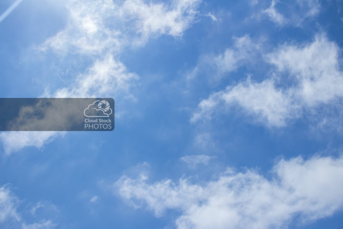 Wispy altocumulus clouds stock photo during summer featuring a puffy cloud formation along the bottom, a sunray beaming down across the top-left corner, and a bright blue sky.