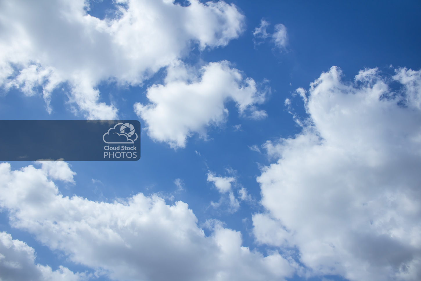 Stock image of a huge cumulus storm clouds that are bright white and gray. Behind the puffy clouds is a bright blue sky across the middle and top-right corner of the image.